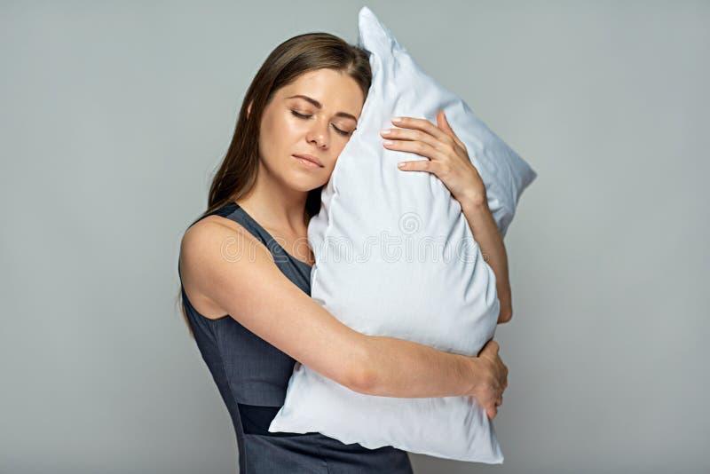 拿着有闭合的眼睛的女商人枕头 免版税库存图片
