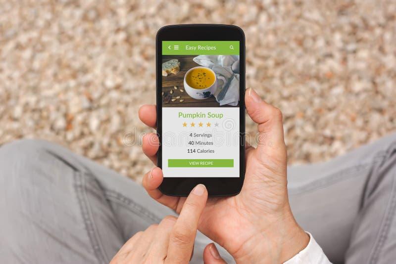 拿着有食物应用嘲笑的手智能手机在屏幕上 库存照片