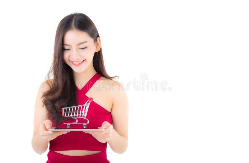 拿着有高兴的女孩和推车的红色礼服的微笑的亚裔妇女片剂在片剂 免版税库存照片