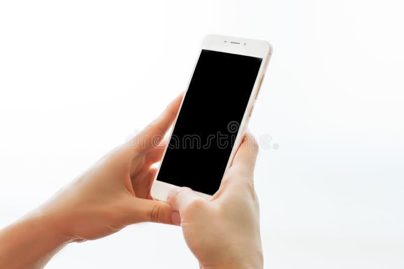 拿着有黑屏幕的女性手智能手机隔绝在白色背景 移动设备关闭  概念的嘲笑 库存图片