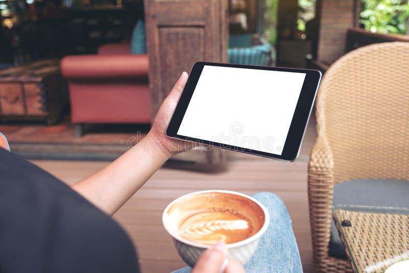 拿着有黑屏的妇女的手白色手机,当喝在现代咖啡馆时的咖啡 免版税库存照片
