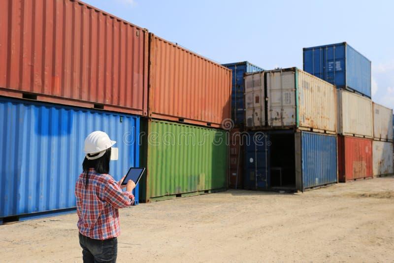 拿着有黑屏的工程师手数字片剂在前面容器和进出口背景、技术和事务 免版税库存图片