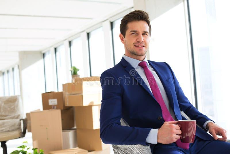 拿着有移动的箱子的年轻商人画象咖啡杯在背景中在办公室 库存照片