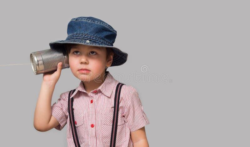 拿着有绳子的小男孩一个罐头 库存照片