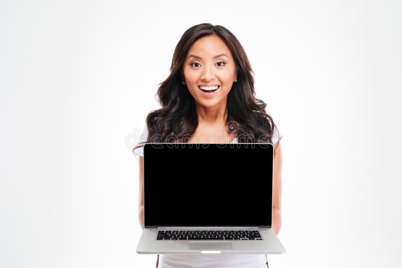拿着有黑屏的愉快的微笑的美丽的亚裔妇女膝上型计算机 免版税图库摄影