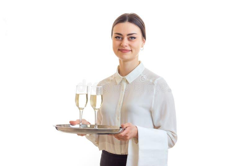 拿着有玻璃的愉快的美丽的女服务员一个盘子酒和微笑 图库摄影