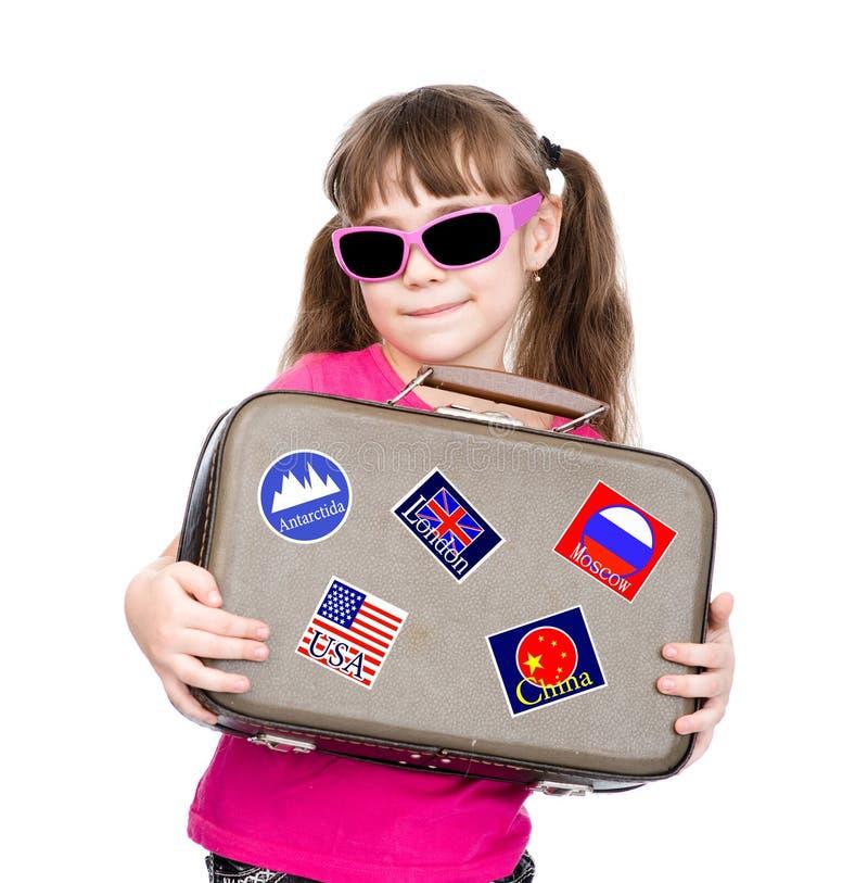 拿着有贴纸的女孩手提箱从各种各样的国家 查出在白色 免版税库存图片