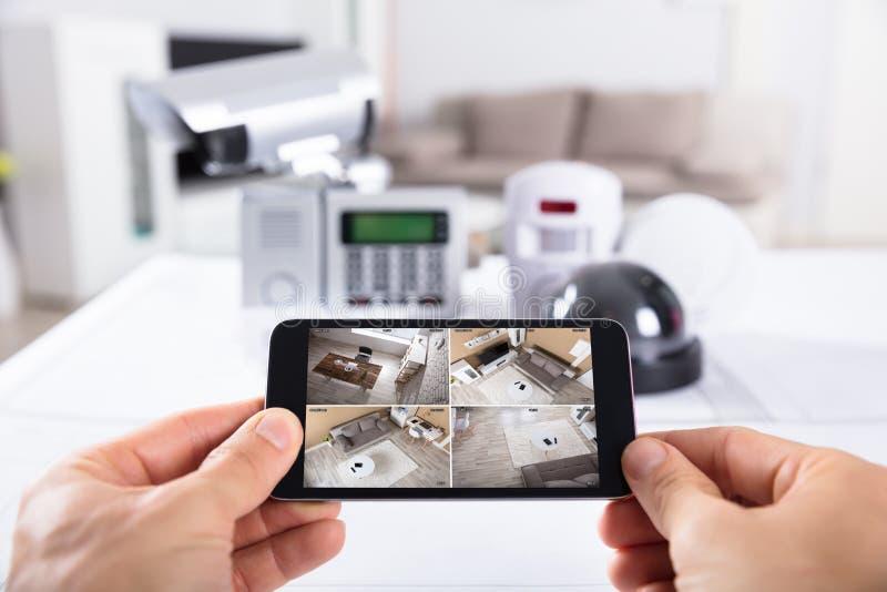 拿着有CCTV照相机英尺长度的人手机在屏幕上 免版税图库摄影