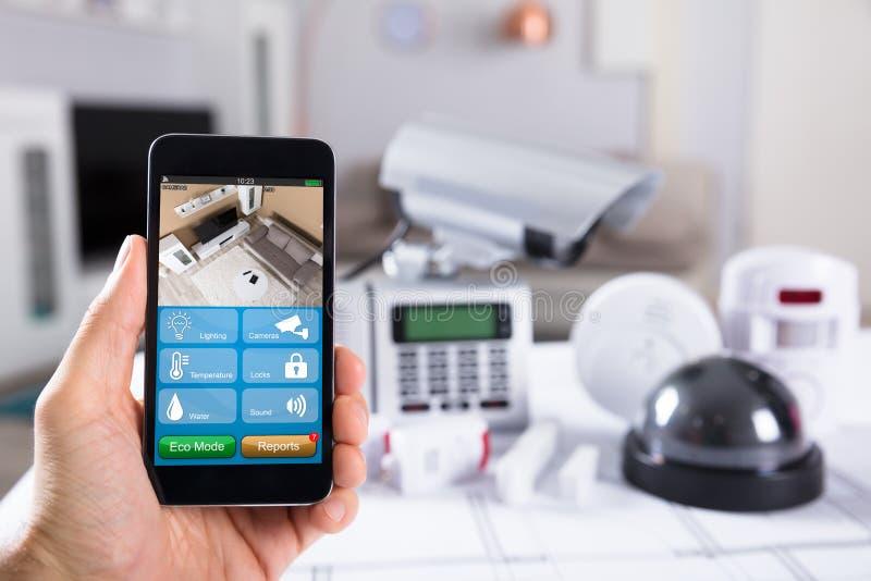 拿着有CCTV照相机英尺长度的人手机在屏幕上 免版税库存图片