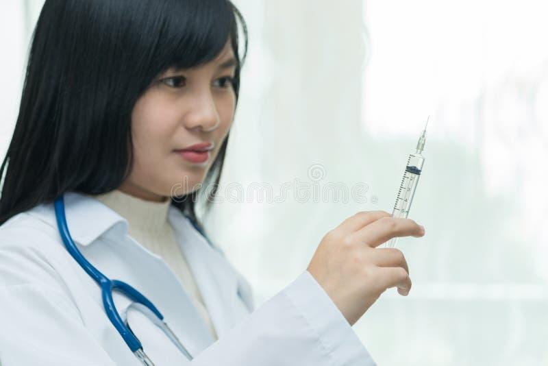 拿着有injec的女性医生或医师注射器 免版税库存照片