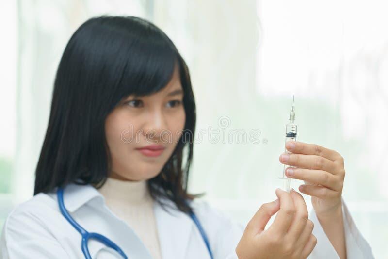拿着有injec的女性医生或医师注射器 库存图片