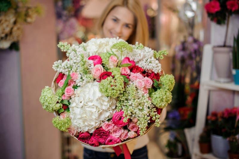 拿着木兰和玫瑰的美丽的花束女孩 免版税图库摄影