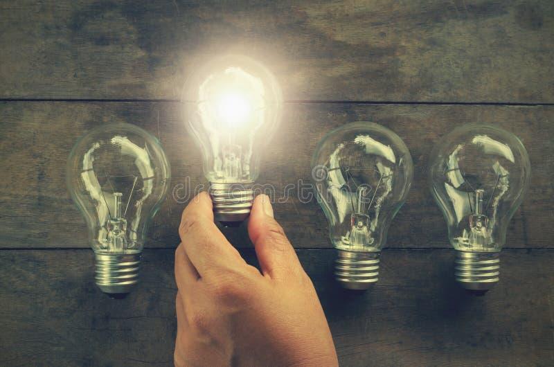 拿着木头的概念电灯泡手中妇女 库存图片