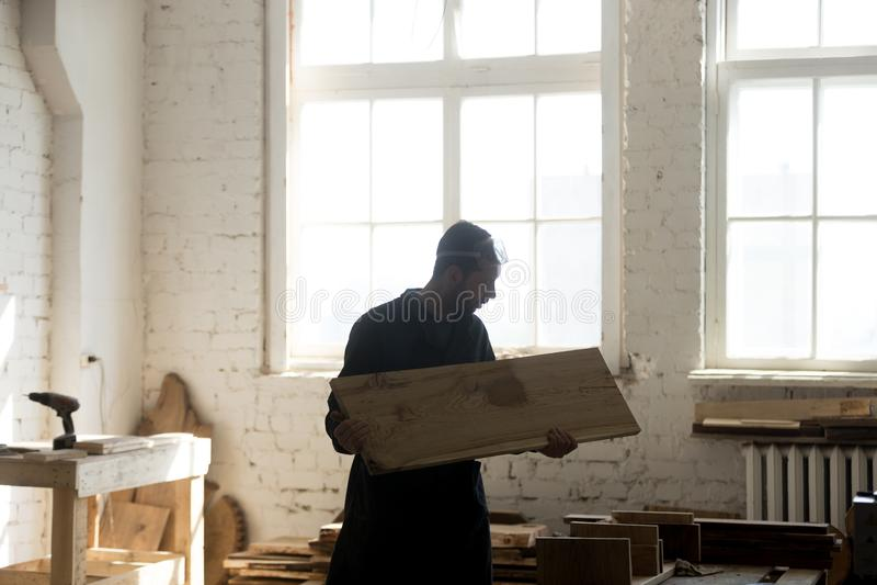 拿着木板,木材加工的年轻木匠在木匠业s方面 图库摄影