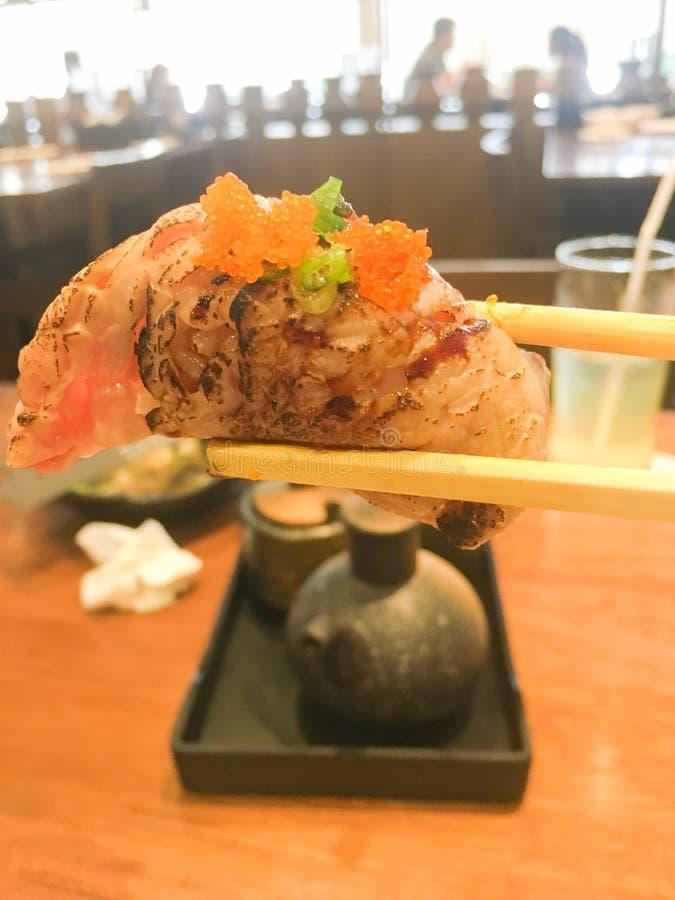 拿着木棍子寿司的手在日本料理店 免版税库存图片