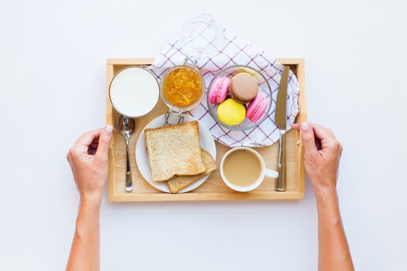 拿着木盘子用蛋白杏仁饼干的女性手 库存图片