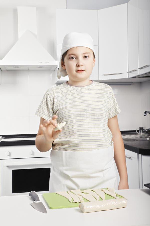 拿着未加工的新月形面包的男孩 免版税库存照片