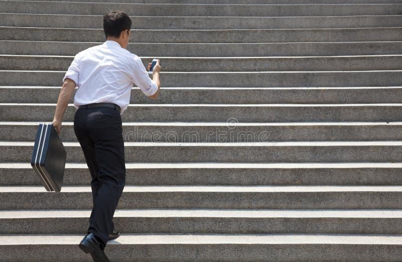 拿着机动性和在仓促的商人跑在台阶 免版税库存照片