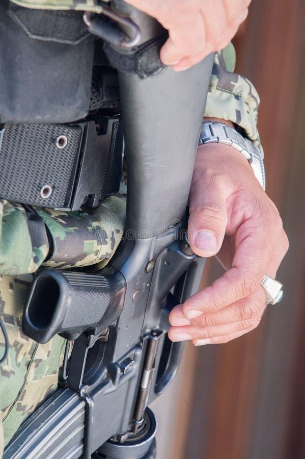 拿着机枪的战士手 免版税库存图片