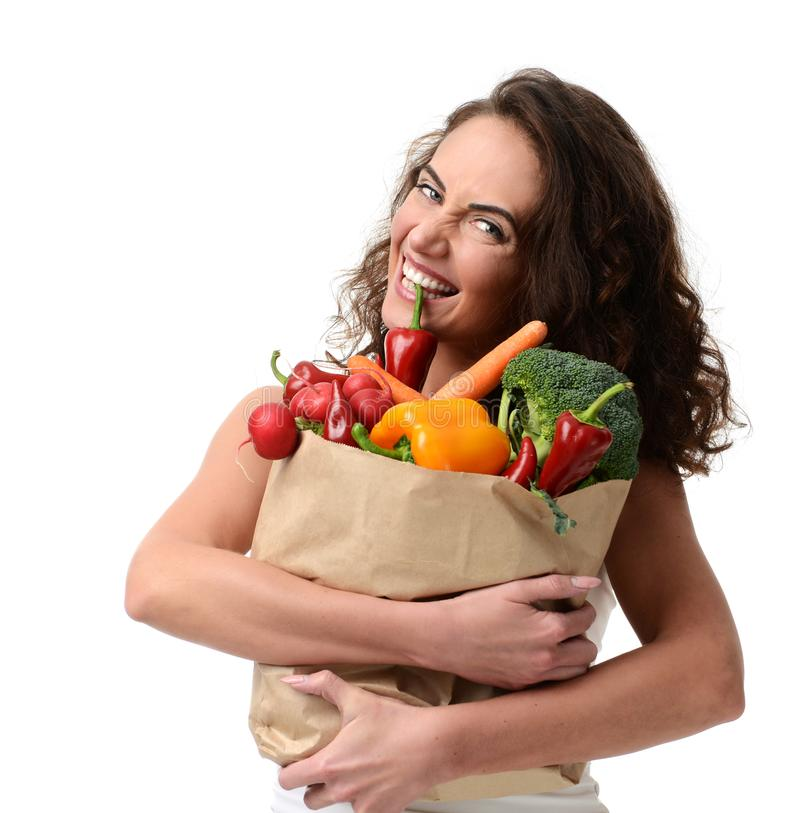 拿着杂货纸购物袋的少妇有很多新鲜蔬菜 免版税库存照片