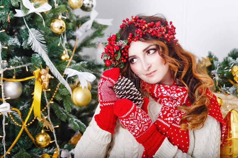 拿着杉木锥体的可爱的女孩在圣诞树 库存图片