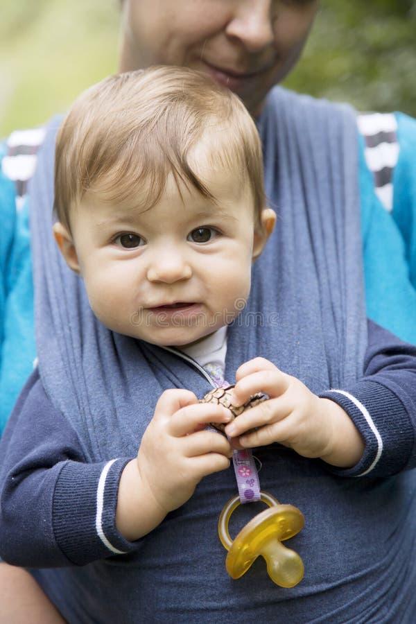 拿着杉木锥体的婴孩特写镜头,当拿着她时的母亲 库存图片