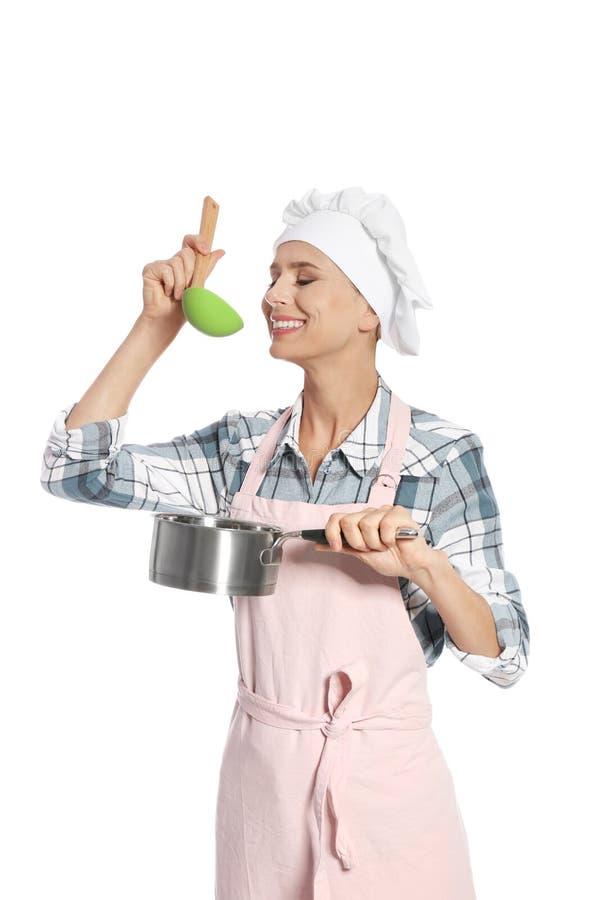 拿着杓子和平底深锅的女性厨师 图库摄影