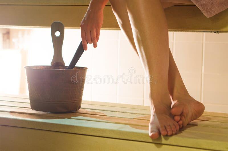 拿着杓子的蒸汽浴的妇女投掷从桶的水到火炉 免版税库存照片