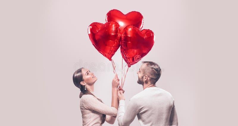 拿着束心形的气球的微笑的秀丽女孩和她英俊的男朋友画象  免版税库存照片