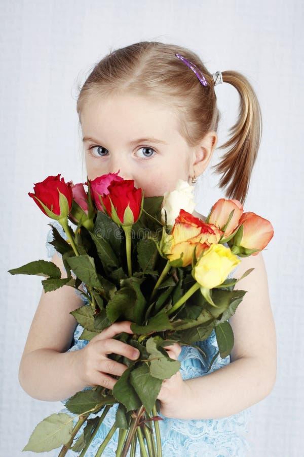 拿着束玫瑰的美丽的小女孩 库存照片