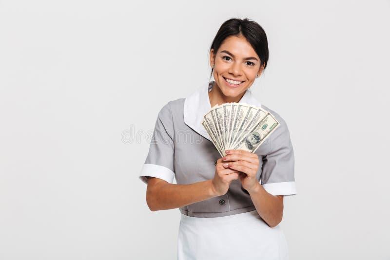 拿着束金钱的年轻可爱的女性佣人画象  库存图片