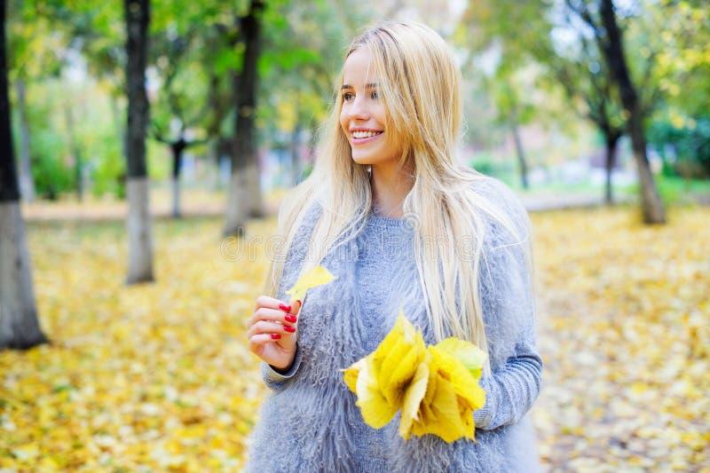 拿着束黄色秋叶的妇女 免版税库存图片