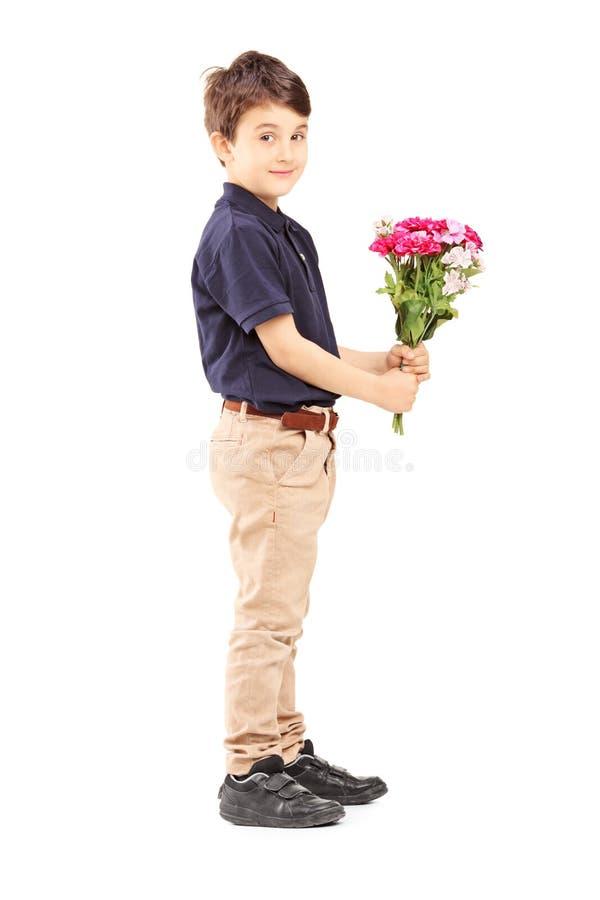 拿着束flowe的一个逗人喜爱的小男孩的全长画象 免版税库存图片