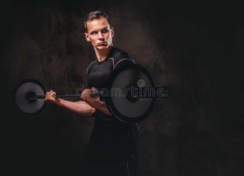 拿着杠铃和做在二头肌的被聚焦的年轻运动员锻炼 查出在黑暗的背景 免版税库存照片
