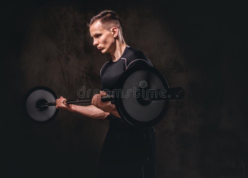 拿着杠铃和做在二头肌的被聚焦的年轻运动员锻炼 查出在黑暗的背景 免版税库存图片