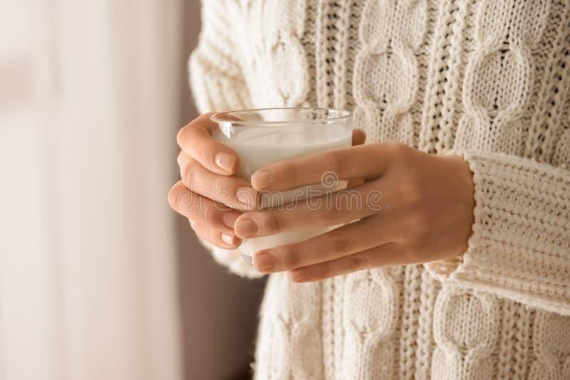 拿着杯可口牛奶,特写镜头的妇女 免版税库存图片
