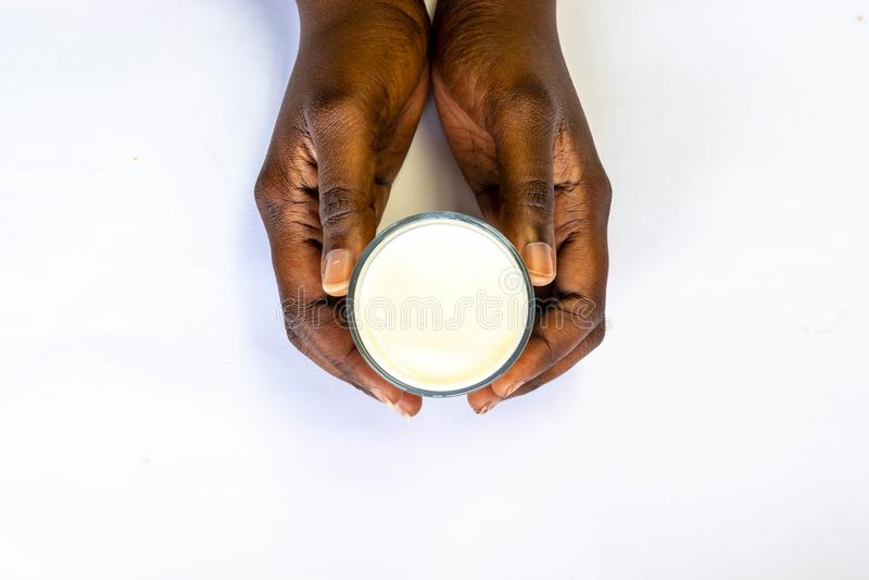 拿着杯在白色背景的温暖的新鲜的牛奶的非洲人的手 顶视图食物和饮料健康概念的 好钙 免版税库存照片