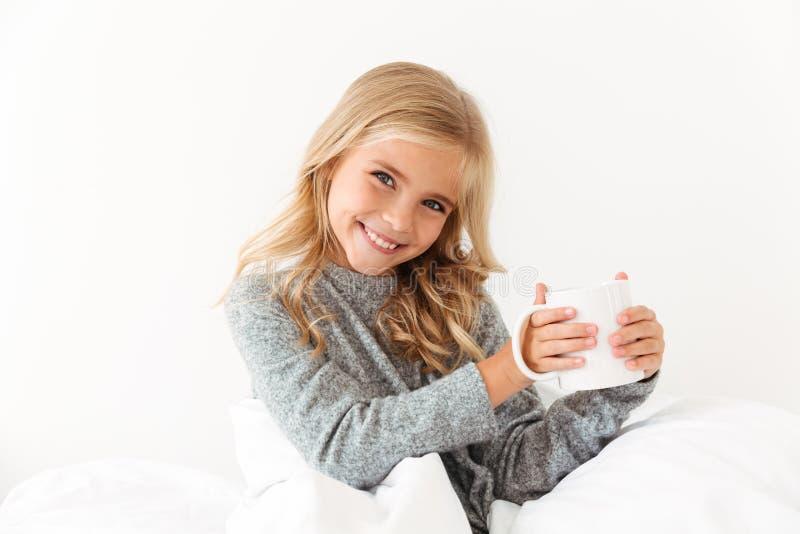 拿着杯子发球区域的快乐的小女孩,看照相机,当时 库存图片