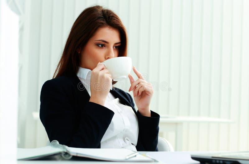 拿着杯子和喝咖啡的年轻微笑的女实业家 库存照片