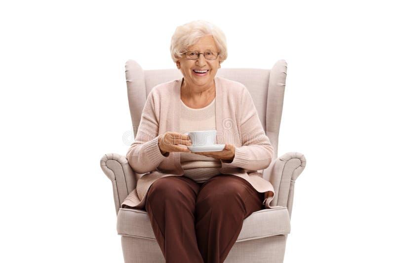 拿着杯子和坐在扶手椅子的资深妇女 图库摄影