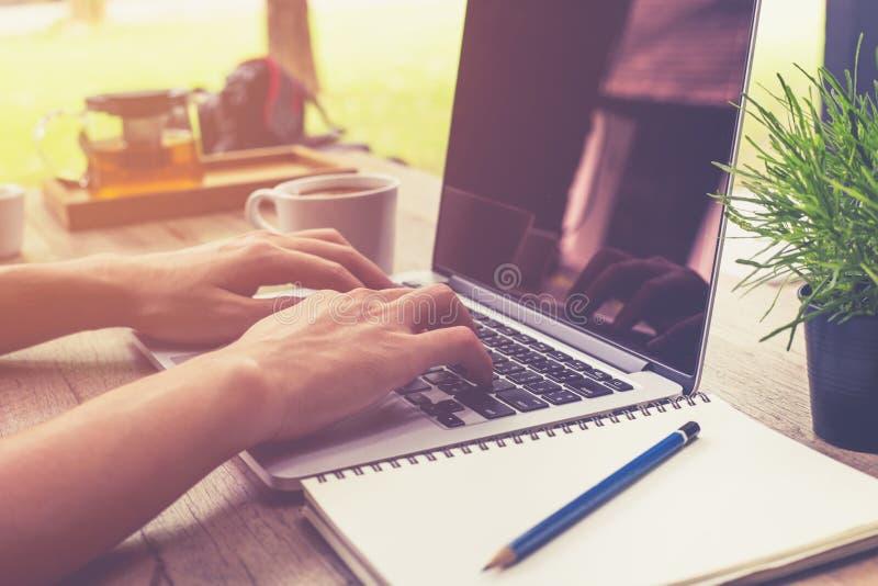 拿着杯子咖啡和使用膝上型计算机comp的年轻商人手 库存照片