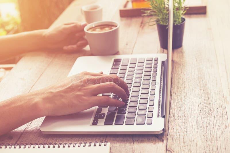 拿着杯子咖啡和使用膝上型计算机comp的年轻商人手 免版税图库摄影