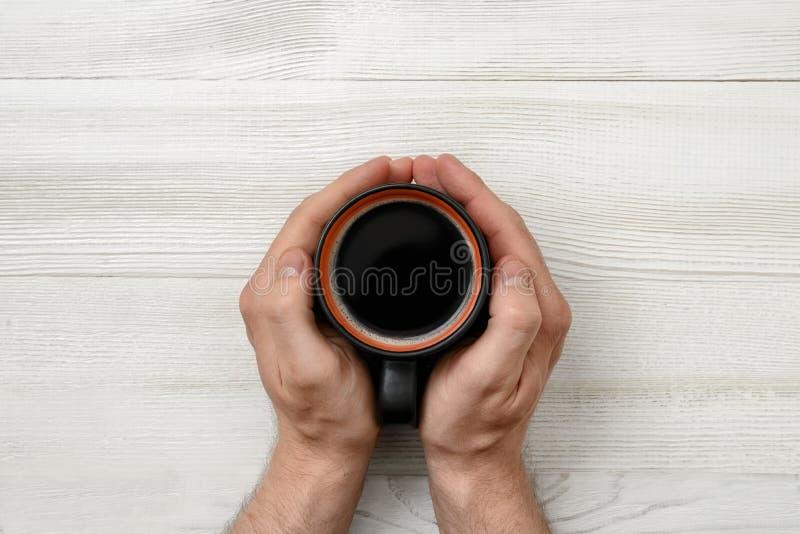 拿着杯子咖啡的人的特写镜头手 免版税图库摄影