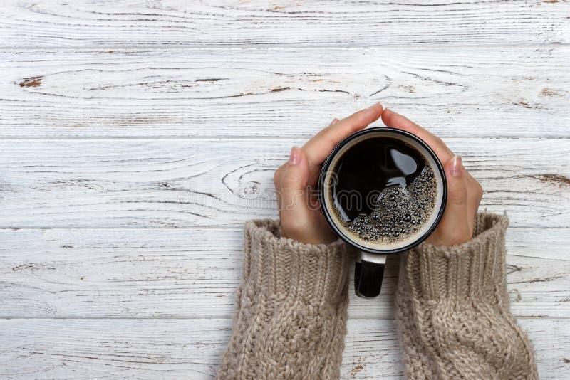 拿着杯子在土气木桌,手特写镜头照片上的热的咖啡的妇女在温暖的毛线衣的有杯子的,冬天早晨概念, t 免版税图库摄影