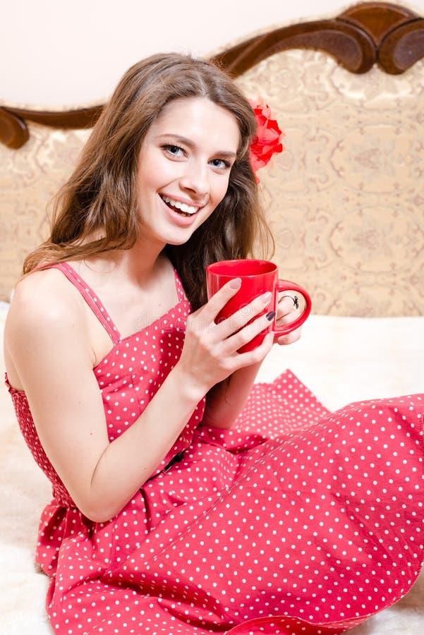 拿着杯子热的红色礼服的饮料美丽的女孩获得放松在床愉快的微笑的&看的乐趣照相机 免版税图库摄影