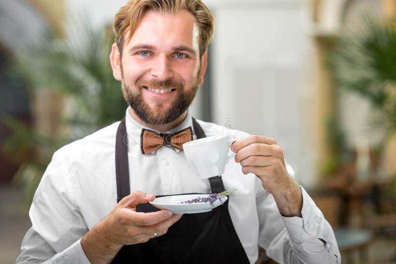 拿着杯子用咖啡的Barista 免版税库存图片