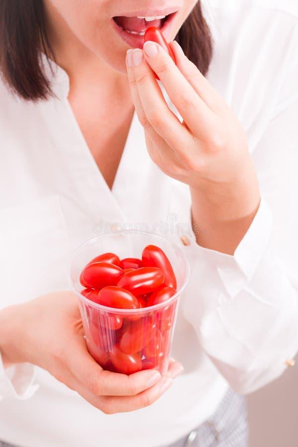 拿着杯子用新鲜的小蕃茄的女实业家 图库摄影