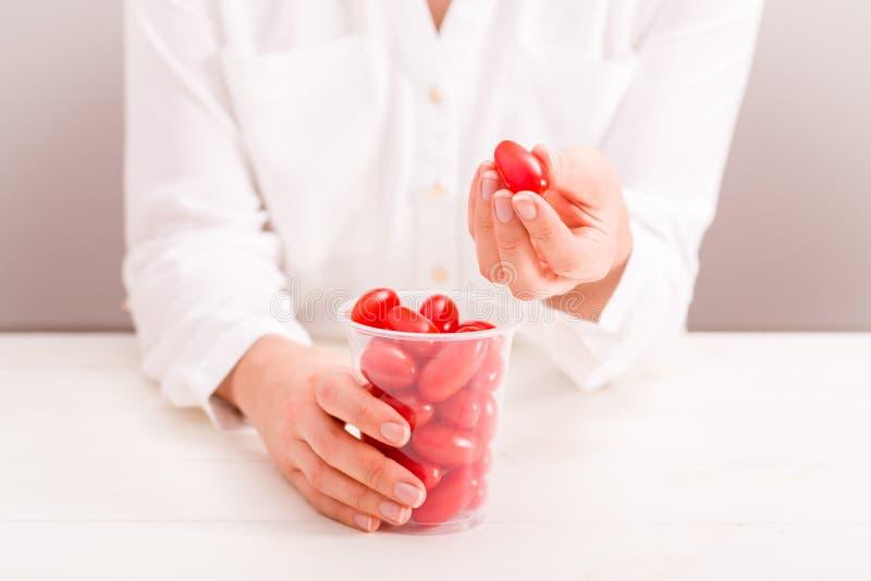 拿着杯子用新鲜的小蕃茄的女实业家 免版税库存图片