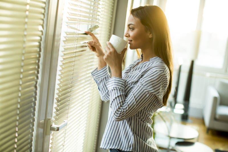 拿着杯子用热的茶或咖啡的可爱的少妇 免版税库存照片