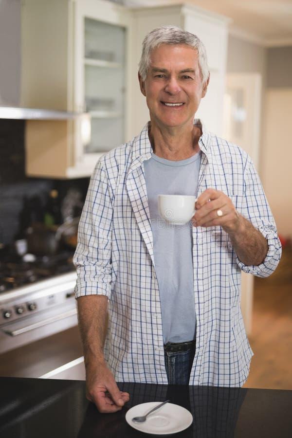 拿着杯子的微笑的老人,当在家时站立在厨房里 免版税图库摄影